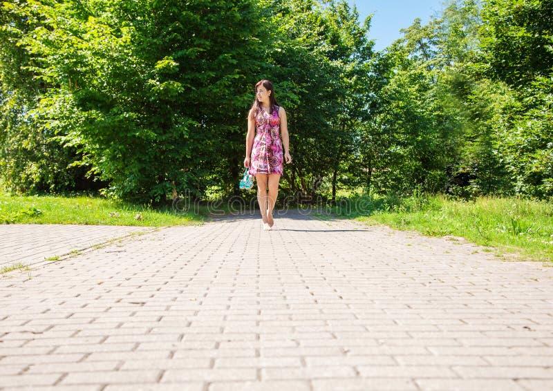 Η νέα γυναίκα πηγαίνει χωρίς παπούτσια στο πεζοδρόμιο στοκ φωτογραφία