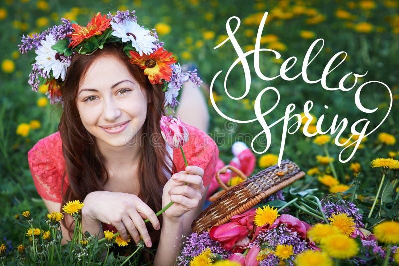 Η νέα γυναίκα που απολαμβάνει τη μυρωδιά σε έναν ανθίζοντας κήπο άνοιξη με τις επιστολές γειά σου τρέχει γρήγορα στοκ εικόνα