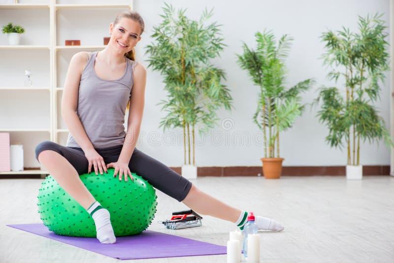 Η νέα γυναίκα που ασκεί με τη σφαίρα σταθερότητας στη γυμναστική στοκ φωτογραφίες με δικαίωμα ελεύθερης χρήσης