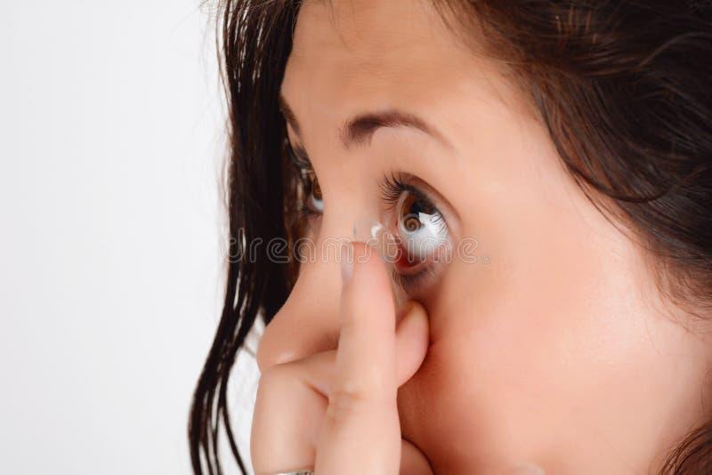 Η νέα γυναίκα που βάζει το φακό επαφής στο σωστό μάτι της, κλείνει επάνω στοκ φωτογραφίες με δικαίωμα ελεύθερης χρήσης