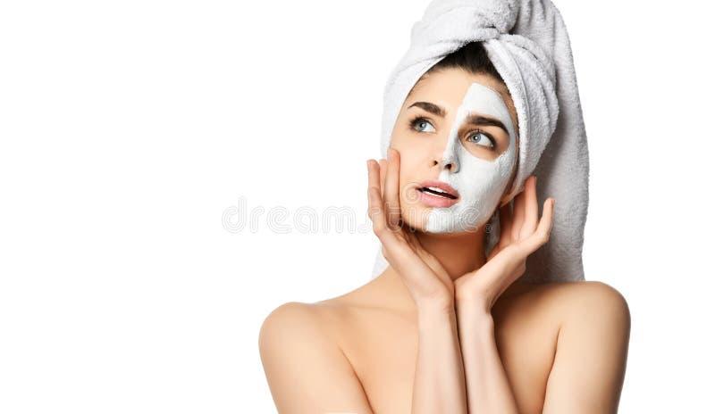Η νέα γυναίκα που είναι αμέσως μετά από το ντους με ακριβώς την εφαρμοσμένη του προσώπου μάσκα αγγίζει το δέρμα της και αισθάνετα στοκ φωτογραφία με δικαίωμα ελεύθερης χρήσης
