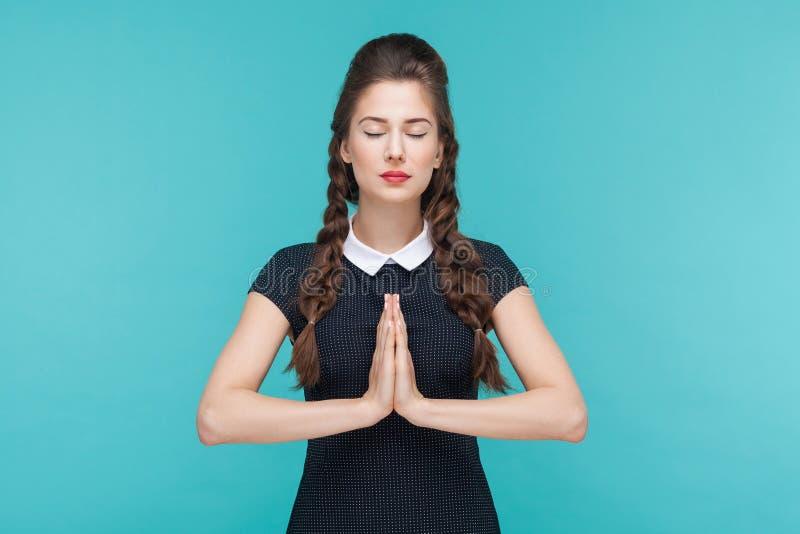 Η νέα γυναίκα που και που κάνει η γιόγκα ή προσεύχεται στοκ εικόνα
