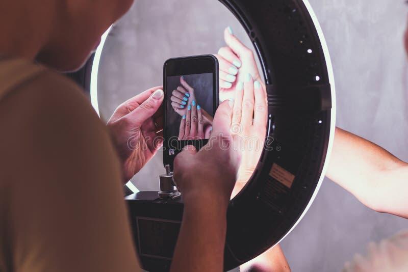 Η νέα γυναίκα που παίρνει τη φωτογραφία το χέρι γυναικών Λήψη της φωτογραφίας των καρφιών στο σαλόνι ομορφιάς στοκ εικόνες
