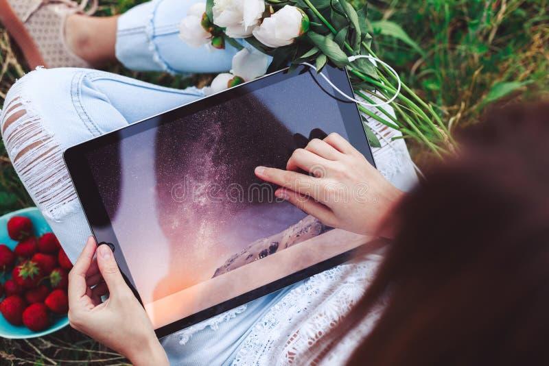 Η νέα γυναίκα που χρησιμοποιεί μια συνεδρίαση PC ταμπλετών στη θερινή χλόη με την ανθοδέσμη των peonies ανθίζει krasnodar διακοπέ στοκ φωτογραφία με δικαίωμα ελεύθερης χρήσης