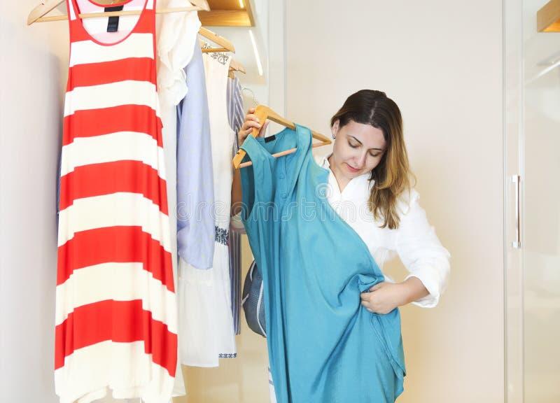 Η νέα γυναίκα προσπαθεί στο φόρεμα στοκ εικόνα