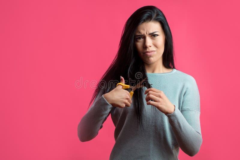 Η νέα γυναίκα πρόκειται να κόψει την τρίχαη στοκ φωτογραφία με δικαίωμα ελεύθερης χρήσης