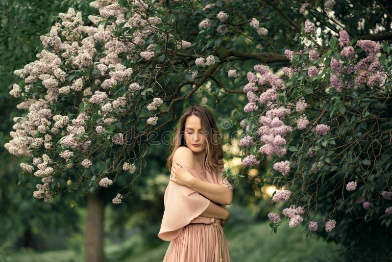 Η νέα γυναίκα σε ένα όμορφο φόρεμα στέκεται κοντά σε έναν ιώδη θάμνο στοκ εικόνες
