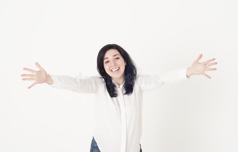 Η νέα γυναίκα σε μια άσπρη μπλούζα προετοιμάζεται να αγκαλιάσει κάποιο, διαδίδει τα χέρια της ευρέως χώρια και χαιρετά το χαμόγελ στοκ φωτογραφία με δικαίωμα ελεύθερης χρήσης