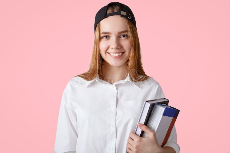 Η νέα γυναίκα σπουδαστής με το θετικό χαμόγελο, φορά τη μοντέρνη ΚΑΠ και το άσπρο πουκάμισο, κρατά το σωρό των βιβλίων, έτοιμο γι στοκ φωτογραφία με δικαίωμα ελεύθερης χρήσης