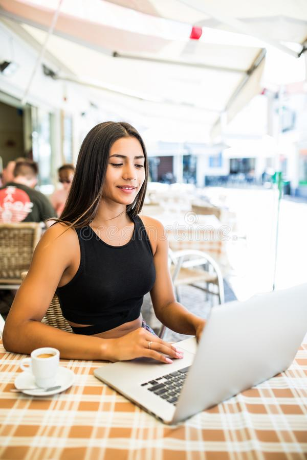 Η νέα γυναίκα σπουδαστής πίνει τον καφέ πληκτρολογώντας στο φορητό προσωπικό υπολογιστή της καθμένος στον καφέ στο καθαρό αέρα στ στοκ φωτογραφία με δικαίωμα ελεύθερης χρήσης