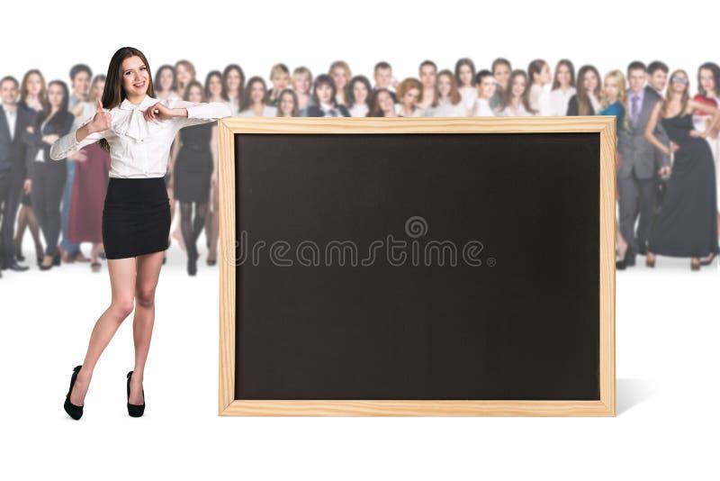 Η νέα γυναίκα στέκεται κοντά στο μεγάλο πίνακα κιμωλίας στοκ φωτογραφίες με δικαίωμα ελεύθερης χρήσης