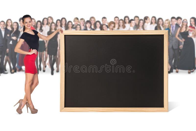 Η νέα γυναίκα στέκεται κοντά στο μεγάλο πίνακα κιμωλίας στοκ εικόνα