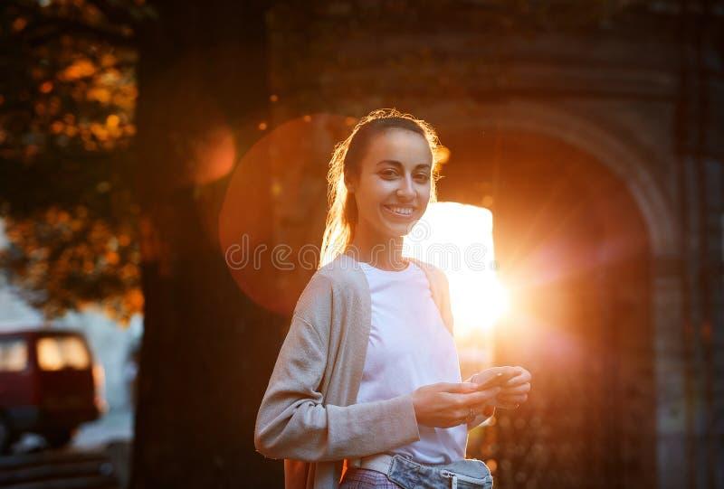 Η νέα γυναίκα στέκεται στην οδό σε ένα όμορφο ηλιοβασίλεμα backlight και χρησιμοποιεί το κινητό τηλέφωνο στοκ εικόνες