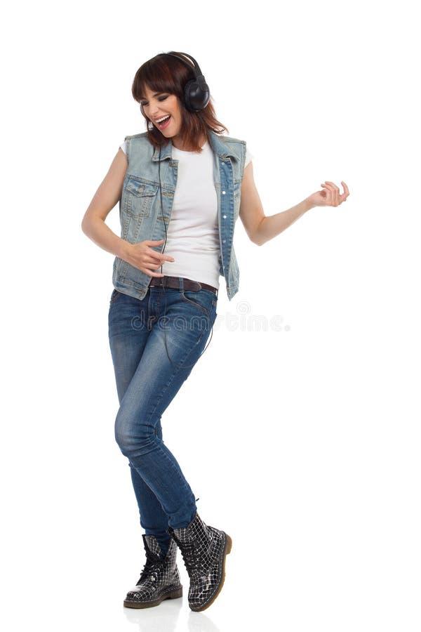 Η νέα γυναίκα στα ακουστικά τραγουδά και παίζει την κιθάρα αέρα στοκ εικόνα