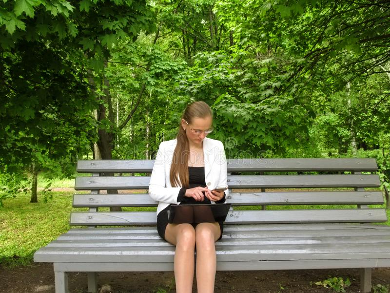Η νέα γυναίκα στα γυαλιά και τα ενδύματα γραφείων εξετάζει το τηλέφωνο καθμένος στο πάρκο σε έναν πάγκο με ένα lap-top στην περιτ στοκ φωτογραφίες