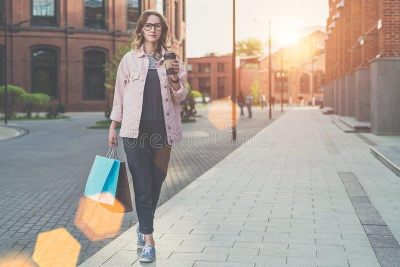 Η νέα γυναίκα στα γυαλιά περπατά κατά μήκος της οδού πόλεων, φέρνοντας τσάντες αγορών και κράτημα του φλιτζανιού του καφέ στοκ φωτογραφία με δικαίωμα ελεύθερης χρήσης