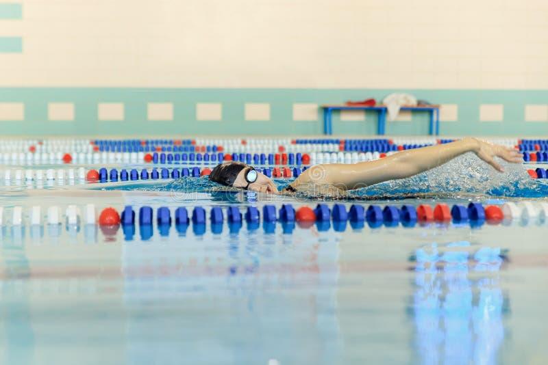 Η νέα γυναίκα στα προστατευτικά δίοπτρα και το κολυμπώντας μέτωπο ΚΑΠ σέρνονται ύφος κτυπήματος στην μπλε λίμνη αγώνων νερού εσωτ στοκ φωτογραφία