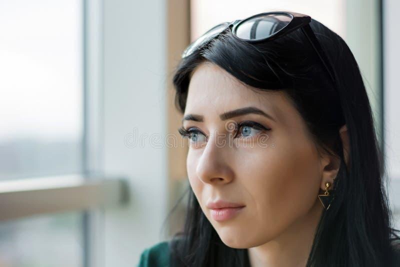 Η νέα γυναίκα στην αναμονή φαίνεται έξω το τεράστιο παράθυρο στην οδό στοκ φωτογραφία με δικαίωμα ελεύθερης χρήσης