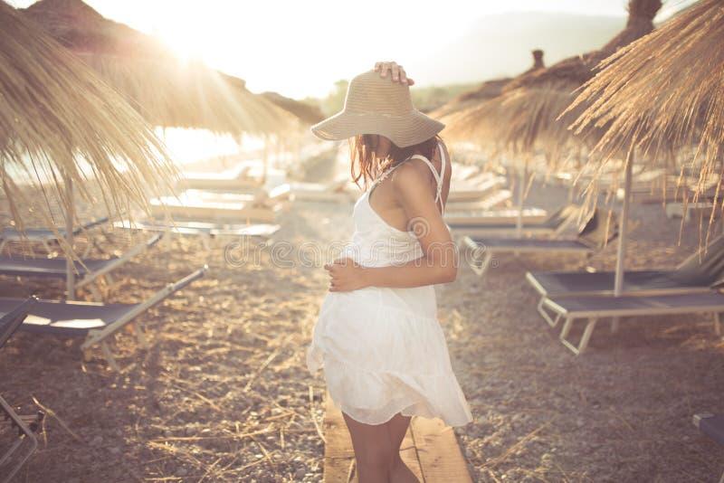 Η νέα γυναίκα στη συνεδρίαση καπέλων αχύρου σε μια τροπική παραλία, απόλαυση στρώνει με άμμο και ηλιοβασίλεμα Τοποθέτηση στη σκιά στοκ φωτογραφία