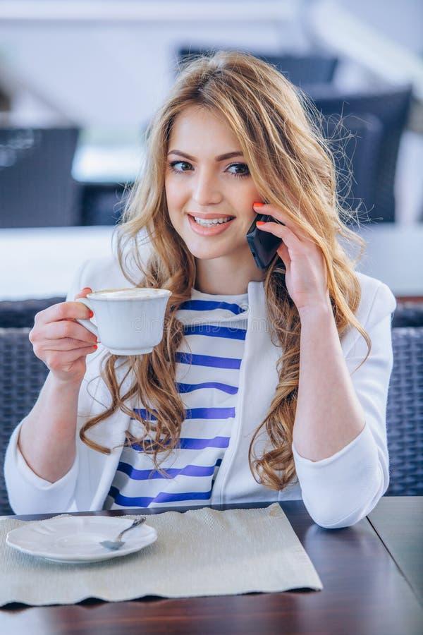 Η νέα γυναίκα στον καφέ πίνει τον καφέ και την ομιλία επάνω στοκ φωτογραφίες