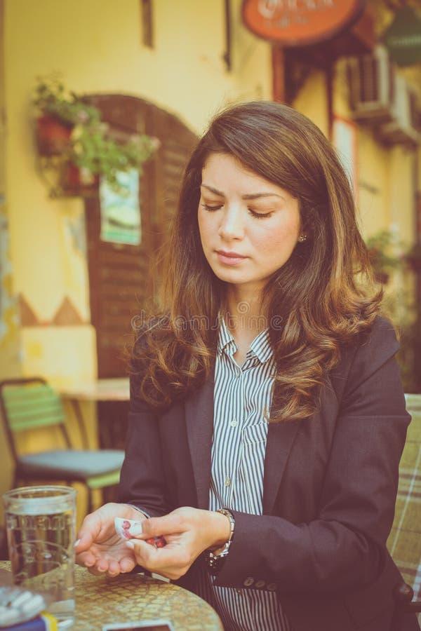 Η νέα γυναίκα στον καφέ, παίρνει τα χάπια στοκ εικόνες