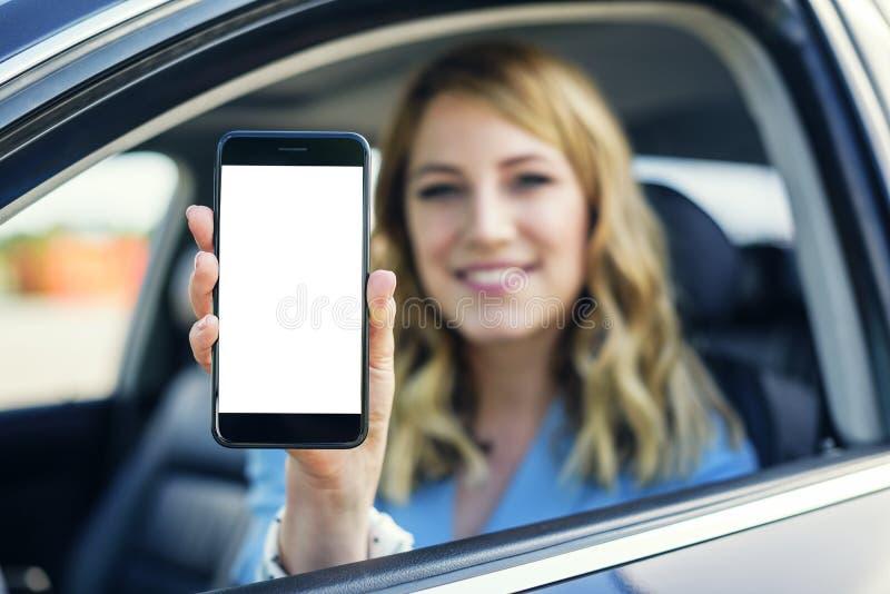 Η νέα γυναίκα στο αυτοκίνητο παρουσιάζει smartphone με την κενή οθόνη στοκ εικόνες