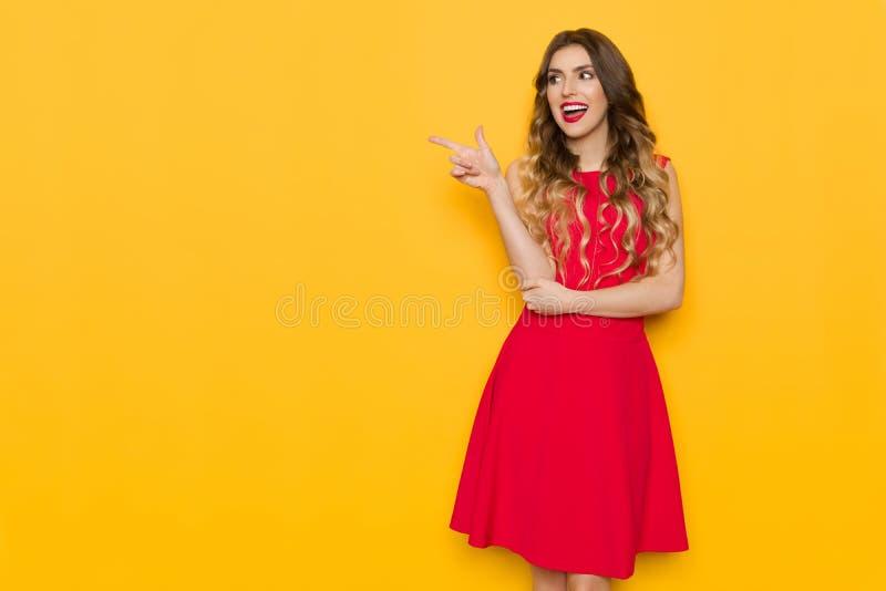 Η νέα γυναίκα στο κόκκινο φόρεμα κοιτάζει μακριά, υπόδειξη και ομιλία στοκ φωτογραφία με δικαίωμα ελεύθερης χρήσης