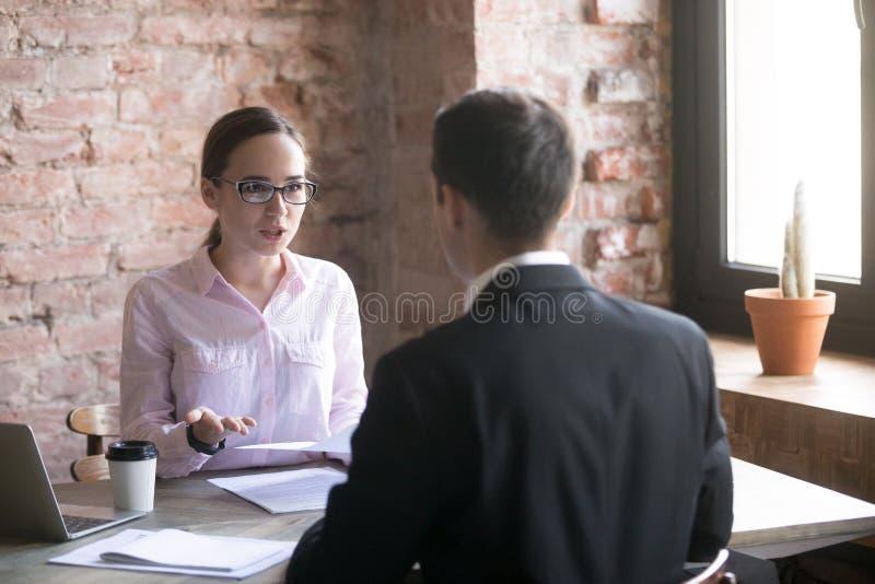 Η νέα γυναίκα συμβουλεύει τον πελάτη, εξηγεί τους όρους της σύμβασης στοκ φωτογραφία με δικαίωμα ελεύθερης χρήσης