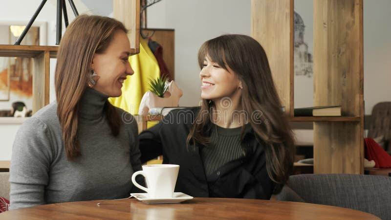 Η νέα γυναίκα συναντιέται στον καφέ για το φίλο που πίνει ένα φλιτζάνι του καφέ στοκ εικόνες