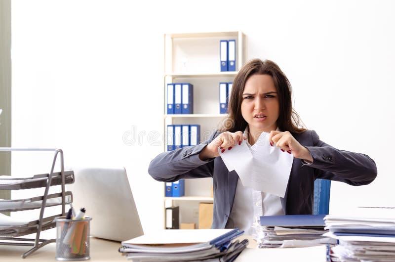 Η νέα γυναίκα υπάλληλος δυστυχισμένος με την υπερβολική εργασία στοκ φωτογραφίες