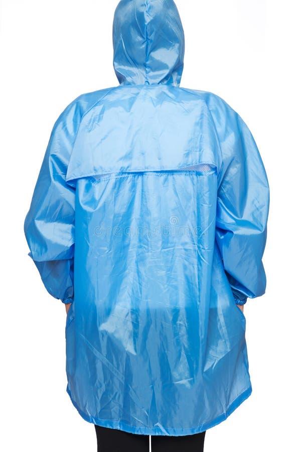 Η νέα γυναίκα φορά το μπλε αδιάβροχο με την κουκούλα στοκ εικόνα