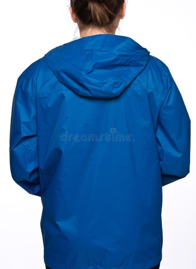 Η νέα γυναίκα φορά το μπλε αδιάβροχο με την κουκούλα στοκ εικόνα με δικαίωμα ελεύθερης χρήσης