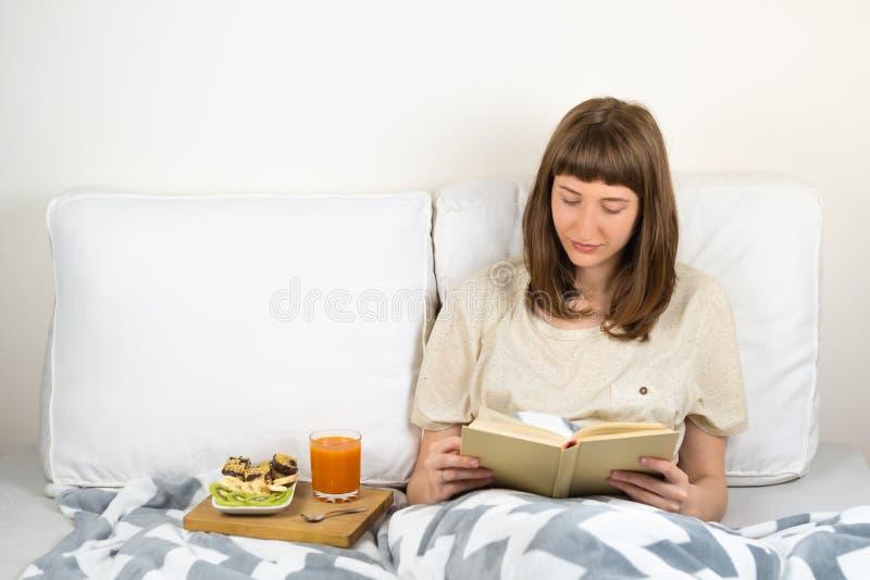 Η νέα γυναίκα χαμογελά και διαβάζει το βιβλίο στο κρεβάτι και έχει το πρόγευμα στοκ εικόνα
