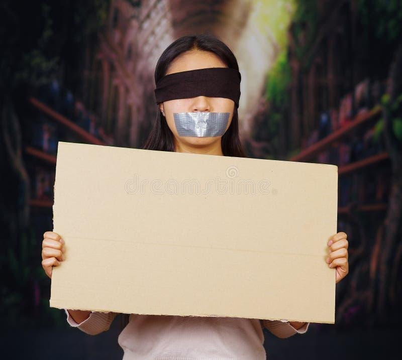 Η νέα γυναίκα brunette που φορά το άσπρο πουλόβερ, το μαύρο σχοινί και φίμωσε με την ταινία αγωγών, κρατώντας ψηλά το κενό σημάδι στοκ φωτογραφίες με δικαίωμα ελεύθερης χρήσης
