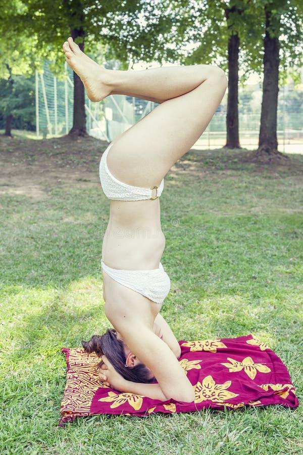 Η νέα γυναίκα handstands σε ένα πάρκο στοκ εικόνες