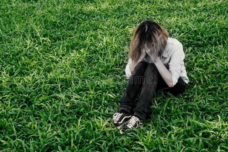 Η νέα γυναίκα hipster, λυπημένη, μακρυμάλλης συνεδρίαση κλείνει το πρόσωπό της στοκ εικόνες