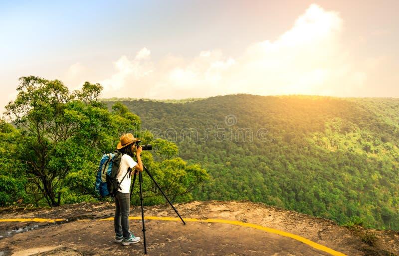 Η νέα διακινούμενη γυναίκα με το καπέλο σακιδίων πλάτης και η κάμερα στο τρίποδο στέκονται στην κορυφή του απότομου βράχου βουνών στοκ φωτογραφίες