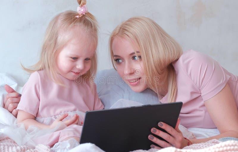 Η νέα ελκυστική ξανθή γυναίκα της διδάσκει λίγη γοητευτική κόρη στα ρόδινα φορέματα χρησιμοποιώντας μια ταμπλέτα βάζοντας στο κρε στοκ εικόνες
