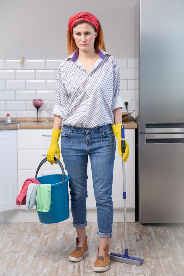 Η νέα ελκυστική τονισμένη γυναίκα υπηρεσιών στα λαστιχένια γάντια πλύσης που φέρνουν την καθαρίζοντας σκούπα και τη σφουγγαρίστρα στοκ εικόνες με δικαίωμα ελεύθερης χρήσης
