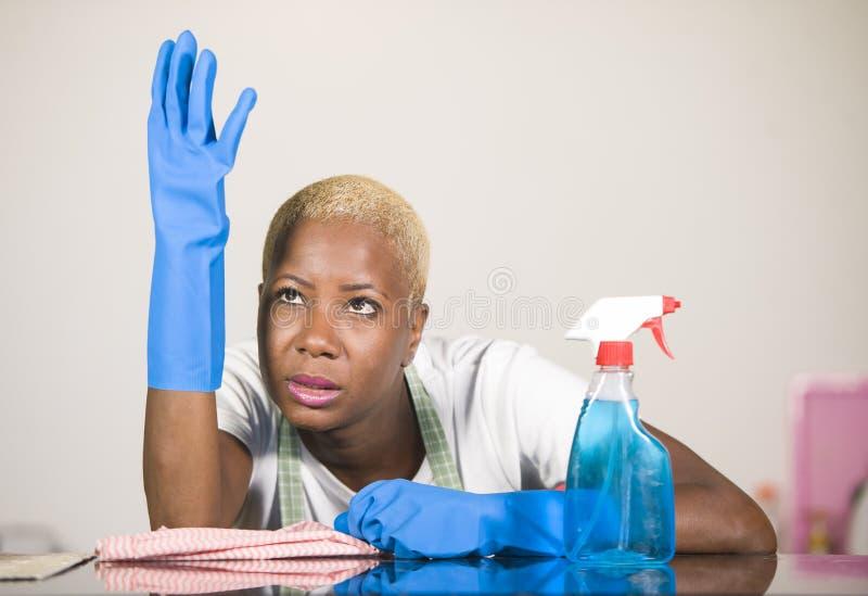 Η νέα ελκυστική τονισμένη και πίσω γυναίκα αφροαμερικάνων στα λαστιχένια γάντια πλύσης που καθαρίζουν την εγχώρια κουζίνα κούρασε στοκ φωτογραφία