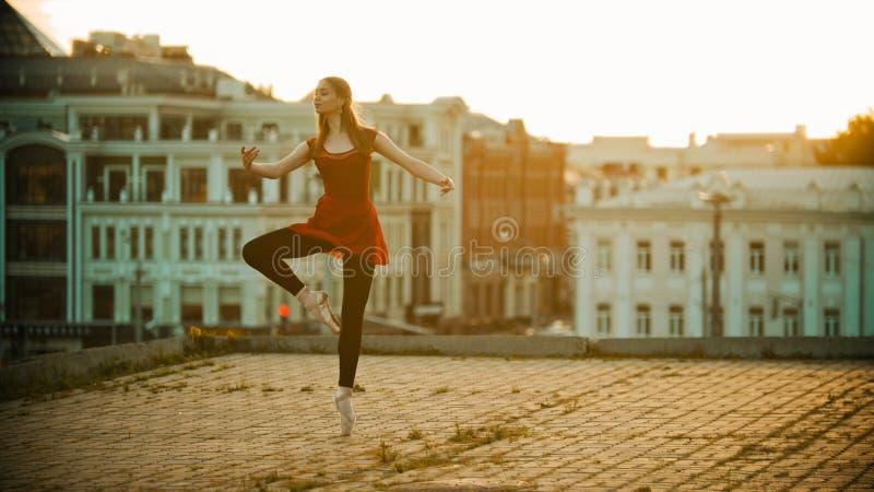 Η νέα εμπνευσμένη γυναίκα στο κόκκινο ballerina φορεμάτων που στέκεται στο χαριτωμένο θέτει στη στέγη - σύγχρονα κτήρια στοκ εικόνα
