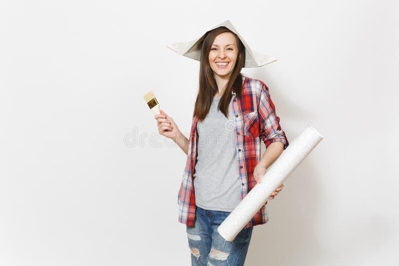 Η νέα ενθουσιασμένη όμορφη γυναίκα στα περιστασιακά ενδύματα και το χρώμα εκμετάλλευσης καπέλων εφημερίδων βουρτσίζουν και ο ρόλο στοκ φωτογραφία