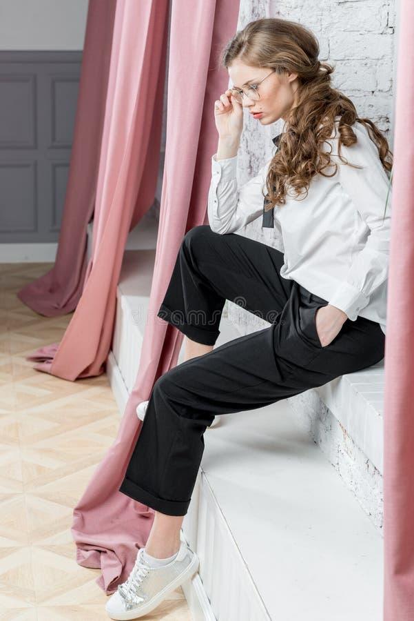 Η νέα επιτυχής επιχειρηματίας στα γυαλιά κάθεται κοντά σε ένα παράθυρο και στοκ φωτογραφία με δικαίωμα ελεύθερης χρήσης