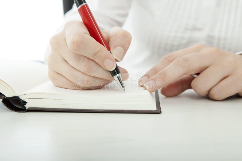 Η νέα επιχειρηματίας γράφει στο βιβλίο στοκ φωτογραφία με δικαίωμα ελεύθερης χρήσης