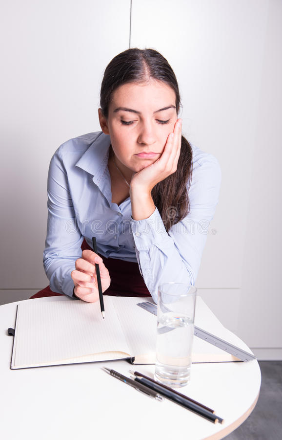 Η νέα επιχειρησιακή γυναίκα που κάθεται τρυπά στο γραφείο στοκ εικόνες