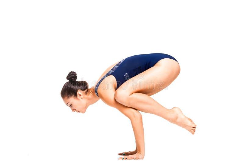 Η νέα λεπτή εύκαμπτη γυναίκα που κάνει τη γιόγκα ισορροπίας βραχιόνων θέτει στοκ εικόνα με δικαίωμα ελεύθερης χρήσης