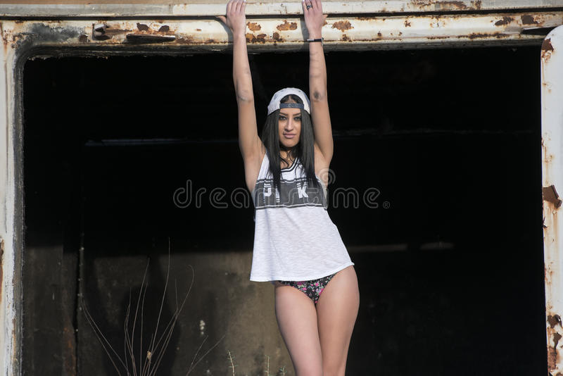 Η νέα λεπτή προκλητική γυναίκα θέτει στην πόρτα ενός βαγονιού εμπορευμάτων τραίνων στοκ εικόνα