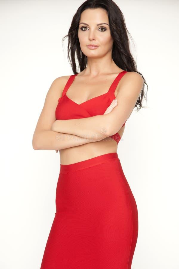 Η νέα λεπτή προκλητική γυναίκα στο κόκκινο φόρεμα στο άσπρο υπόβαθρο στοκ φωτογραφία με δικαίωμα ελεύθερης χρήσης