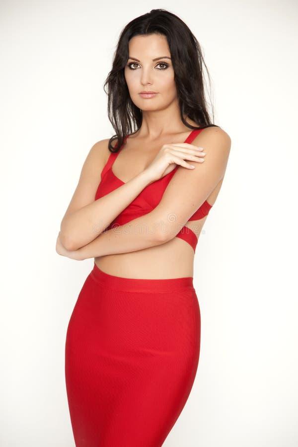 Η νέα λεπτή προκλητική γυναίκα στο κόκκινο φόρεμα στο άσπρο υπόβαθρο στοκ εικόνες