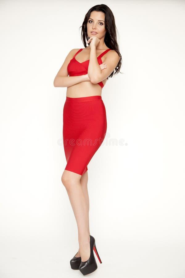 Η νέα λεπτή προκλητική γυναίκα στο κόκκινο φόρεμα στο άσπρο υπόβαθρο στοκ εικόνες με δικαίωμα ελεύθερης χρήσης
